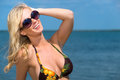 Beautiful blond woman in sunglasses and bikini relaxing and smiling while enjoying the summer sun at the seaside while on a Stock Photos