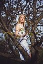 Beautiful blond woman in tree branches, dressed in white dress looking forward
