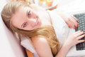 Beautiful blond young business woman blue eyes girl sitting in bed with laptop computer happy smiling looking at camera elegant Royalty Free Stock Photos