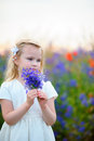 Beautiful blond young girl on green field with flowers Royalty Free Stock Photo