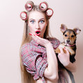 Beautiful blond young pinup woman blue eyes girl having fun playing with cute small dog looking at camera Royalty Free Stock Photo