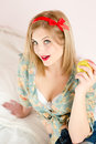 Beautiful blond young woman blue eyes sexy pinup girl holding apple looking at camera sitting in white bed picture of Royalty Free Stock Image