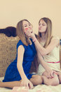 2 beautiful blond young woman, sisters or best pretty girlfriends having fun in bed teasing each other happy smiling relaxing Royalty Free Stock Photo