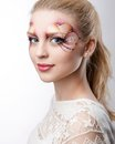 The beautiful blonde with artistic make up on white background Royalty Free Stock Photography
