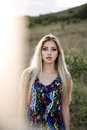 Beautiful blonde with beautiful eyes in blue overalls in nature, sunset sun Royalty Free Stock Photo