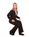 A beautiful blonde blady dressed in black business attire is sitting on an invisible chair the photo has been isolated on white Stock Photography
