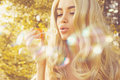 Beautiful blonde blowing bubbles outdoors fashion photo of Royalty Free Stock Photography