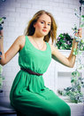The beautiful blonde with blue eyes in the green dress on a swin swing flowers Stock Photo