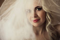 Beautiful blonde bride daylight studio shot emotive portrait of a smiling with vapory white veil close up Royalty Free Stock Image