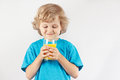 Beautiful blonde child with a glass of fresh orange juice on white background Royalty Free Stock Photo
