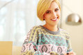 Beautiful blonde in colourful sweater happy at home Stock Images