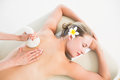 Beautiful blonde enjoying a herbal compress massage at the health spa Stock Image