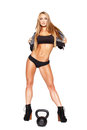 Beautiful blonde fitness model with kettlebell Royalty Free Stock Photography