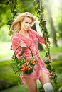 Beautiful blonde with flowers basket in leafy swing Royalty Free Stock Photo