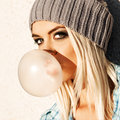 Beautiful blonde girl in beanie hat with smokey eye make up who close of young blond blows big bubble from bubble gum Stock Photo