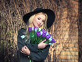 Beautiful blonde girl in a black hat is enjoying tulips bouquet romantic of white and purple beauty fashionable received Royalty Free Stock Photo