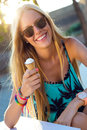 Beautiful blonde girl eating ice cream in city park outdoor portrait of Stock Photos
