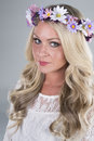 Beautiful blonde girl with flower head piece a poses a white dress and a in studio Stock Images