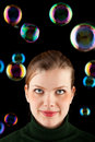 Beautiful blonde girl making colorful soap bubbles Stock Photography