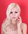 Beautiful blonde girl with pearl necklace on red Stock Image