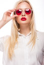 Beautiful blonde girl in pink glasses and shirt. Beauty face. Isolated on white background. Royalty Free Stock Photo