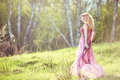 Beautiful blonde girl in pink long dress on a background of nature Royalty Free Stock Photo