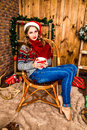 Beautiful blonde girl in a santa hat sitting on a chair with cup his hands room with wooden walls christmas and new year Royalty Free Stock Images