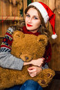 Beautiful blonde girl in a santa hat sitting on a chair with teddy bear her hands room with wooden walls christmas and Stock Photos