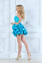 Beautiful blonde girl in short blue dress. Stock Photo