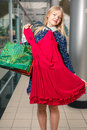 Beautiful blonde girl trying new dress on mall