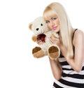 Beautiful blonde girl wearing pajamas embraces teddy bear Royalty Free Stock Photo