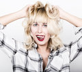 Beautiful blonde girl wearing a plaid shirt showing tongue and clutched his hands in her hair Royalty Free Stock Photo