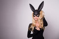 Beautiful blonde haired young woman in carnival mask ballroom rabbit with long ears sensual sexy in a black dress standing Royalty Free Stock Image
