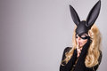 Beautiful blonde haired young woman in carnival mask ballroom rabbit with long ears sensual sexy in a black dress standing defian Stock Photography
