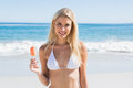 Beautiful blonde holding ice lolly at the beach Royalty Free Stock Photo
