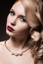 Beautiful blonde in a hollywood manner with curls red lips beauty face picture taken the studio Royalty Free Stock Image