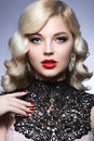 Beautiful blonde in a hollywood manner with curls red lips and lace dress beauty face picture taken the studio on white Royalty Free Stock Images