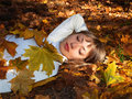 Beautiful blonde with leaves in the autumn forest Royalty Free Stock Photos