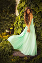 Beautiful blonde with a long curly hair in a long evening dress in static outdoors near retro vintage building in summer sunset