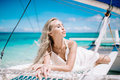 stock image of  Beautiful blonde long hair bride on wedding day ready for travel by sail boat. Happy island lifestyle. White sand, blue cloudy sky