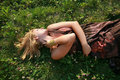 Beautiful blonde lying on the grass Royalty Free Stock Image