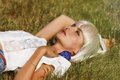 The beautiful blonde lying on the grass with blue rose in his hand in sunshine Royalty Free Stock Image