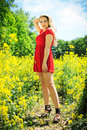 Beautiful blonde in oilseed rape red dress posing fashion photography Stock Photography