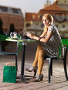 Beautiful blonde rests on a coffee held after a shopping session in downtown Stock Image