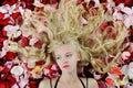 Beautiful blonde in rose petals Stock Photo