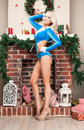 Beautiful blonde Snow Maiden sexy young woman in a blue suit and at brick fireplace, long beautiful legs in high heels. New year, Royalty Free Stock Photo