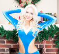 Beautiful blonde snow maiden sexy young woman in a blue suit hands behind head at the christmas tree a brick fireplace new year Stock Photo