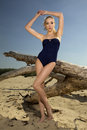Beautiful blonde woman in black swimwear posing on a log Royalty Free Stock Photos