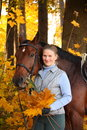 Beautiful blonde woman and brown horse in autumn Stock Photos