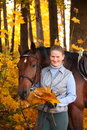 Beautiful blonde woman and brown horse in autumn Royalty Free Stock Photo